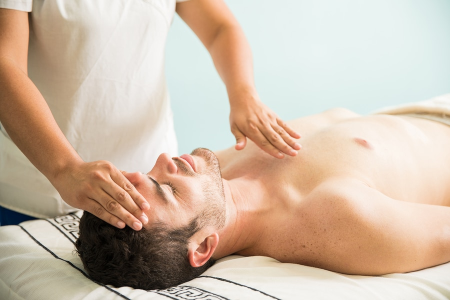bigstock-Reiki-Therapy-On-A-Young-Man-212992810
